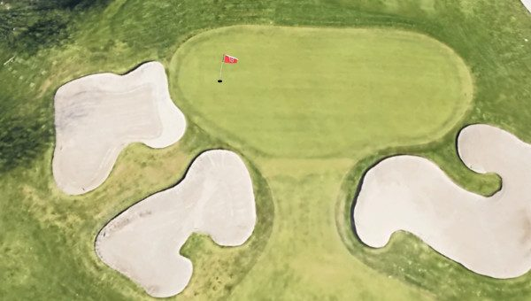 birds eye view of a golf hole with flag on the left side of the green